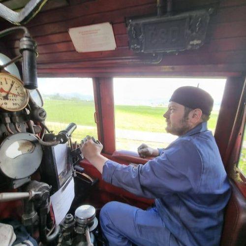 Rušňovodič spomienkového vlaku sústredený na trať a rušeň.